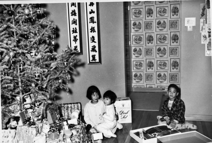 Christina, Jana, and Eugene Ng with Christmas tree beside Chinese wall hangings, circa 1960.  (MS 362: 076-0465)