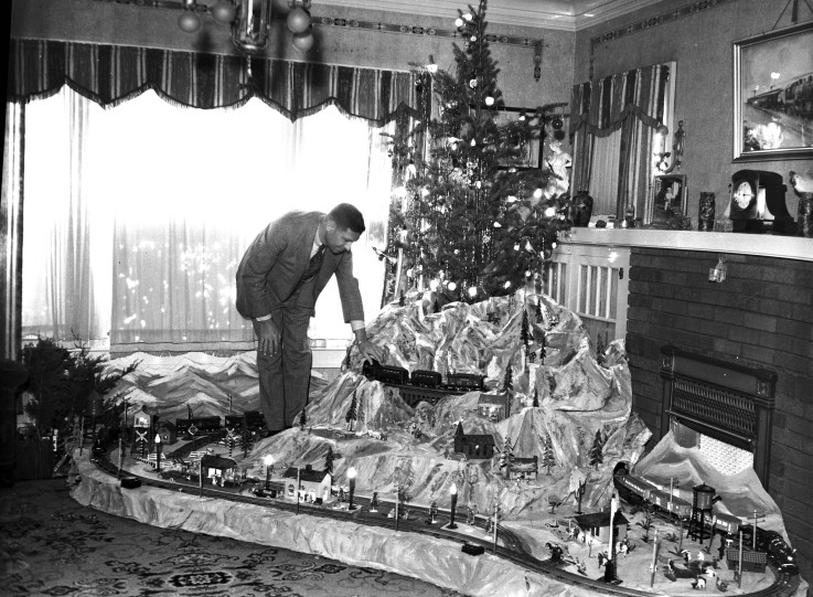 A.G. Sherrer with three electric trains that move on tracks around his Christmas tree, 1936.  (MS 359:  L-1527-E)