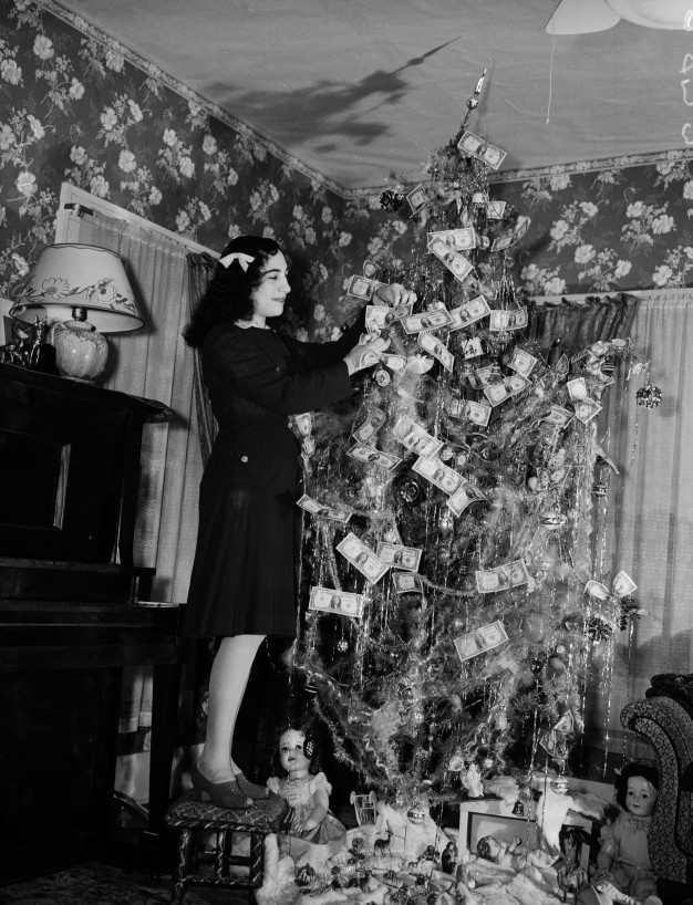 Louise Yuse  with Christmas tree decorated with banknotes that will be used to purchase war bonds, 1942.  (MS 359: L-2877-F)