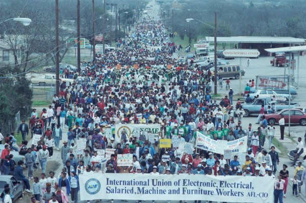 Signs, banners, and political messages are carried by some of the participants as they march along Martin Luther King Boulevard in the second annual Freedom March, January 18, 1988. (MS 360: E-1988-1-18B-36)