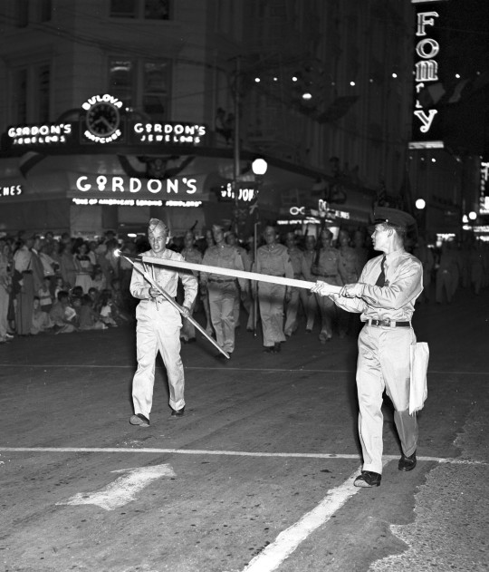 ROTC cadets carry torch sparklers to light the way for marchers.  (MS 359: L-3560-B-1)