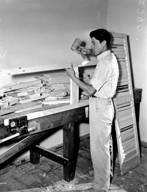 Henry Salazar constructs a facsimile of an original window shutter in NYA arts and crafts shop, January 1940.   (MS 359: L-2340-G)