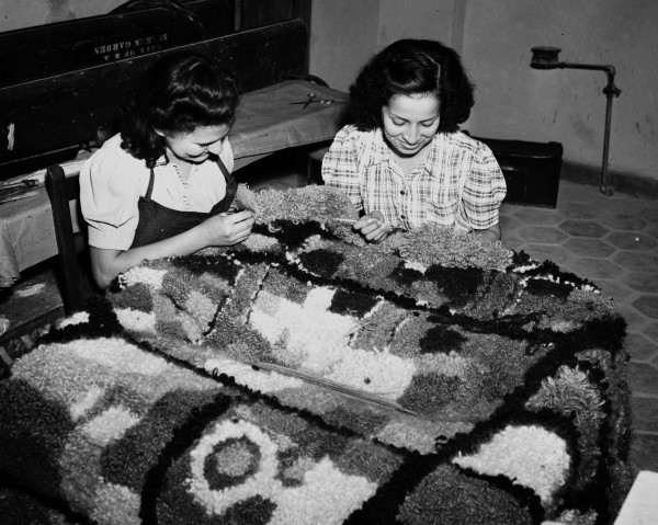 Oralia Flores (left) and Stella Toscano, NYA students, work on hooked rug in new weaving building at La Villita, September 1940.  (MS 359: L-2690-A)