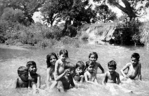 Children swim in the San Antonio River as parents visit on the river bank during Escobedo family gathering, Berg's Mill, early 1950s.  (MS 362:  108-1010)