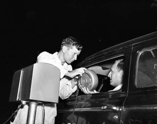 Attendant Bud Grote hands an in-car speaker to Thomas Speakman at San Pedro Outdoor Theatre, May 1948.  (MS 359:  L-3571-D)