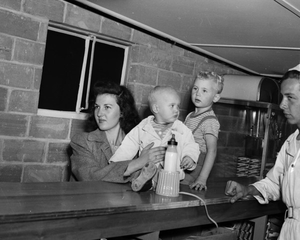 Mrs. J. M. McIntyre follows movie from concession stand as she heats baby's milk with bottle warmer, May 1948.  (MS 359:  L-3571-J)