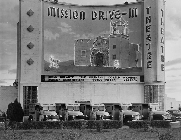 Foremost milk employees pose below neon mural depicting nearby Mission San Jose, Mission Drive-In Theatre, 3100 Roosevelt Avenue, 1950.  (MS 355:  Z-0738)