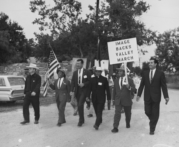Joining the San Antonio segment of the march is H. S. (Hank) Brown (third from left), president of the Texas AFL-CIO.  He is walking between Rev. Novarro and Father Gonzales as they approach Mission San Juan Capistrano, San Antonio, August 26, 1966.   (MS 360: E-0012-187-C-02)