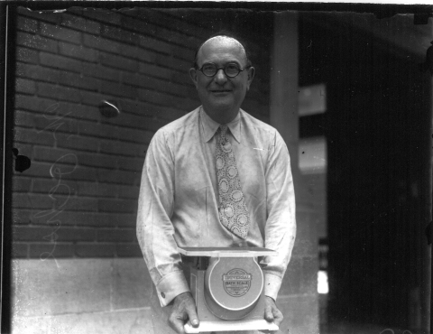 William Ochse holding an empty scale, 1929