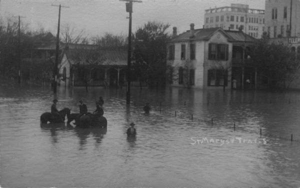 Water covers the yards of rooming houses in the 200 block of E. Travis Street, October 1913.  (MS 362:  097-0895)