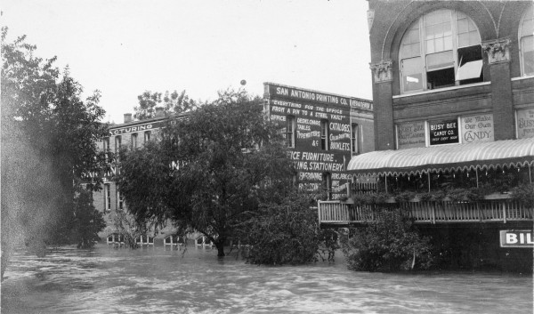 A swollen San Antonio River as seen from the Houston Street Bridge, December 1913.  Book Building on  right.   (MS 362:  099-0510)