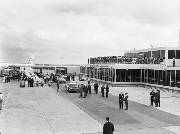 Crowd waits for the President to get in his limousine, parked below the airport observation deck.  Air Force One is in the background.  (MS 360:  E-0009-140-B-09)