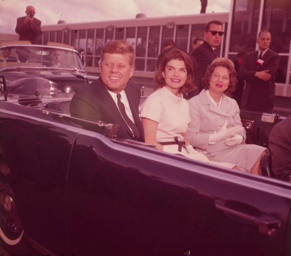 President and Mrs. Kennedy and Nellie Connally are seated in the Presidential Lincoln limousine shortly before departing from the airport.  Governor Connally's shoulder is visible on far right.  (MS 360:  E-0009-140-B-16)