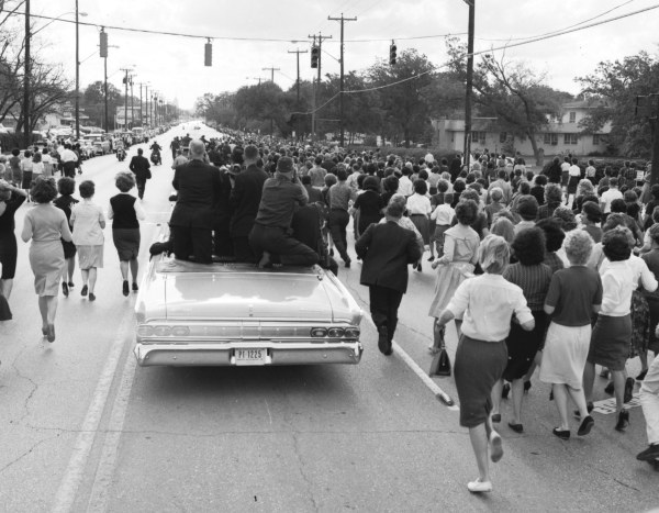 Once again the motorcade makes an unplanned stop when USAA employees break through the police barriers and rush forward to shake President Kennedy's hand.  (MS 360:  E-0009-140-C-10)