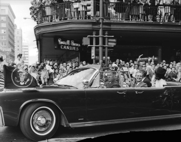 Jacqueline Kennedy waves to the crowd on the balcony of the Gunter Hotel as the motorcade turns from Houston Street to St. Mary's Street.  (MS 360:  E-009-140-D-15)