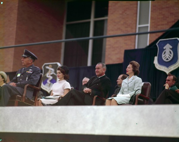 Vice-President Johnson sits between Jacqueline Kennedy and Nellie Connally during the President's speech.  (MS 360:  E-0009-141-A-08)