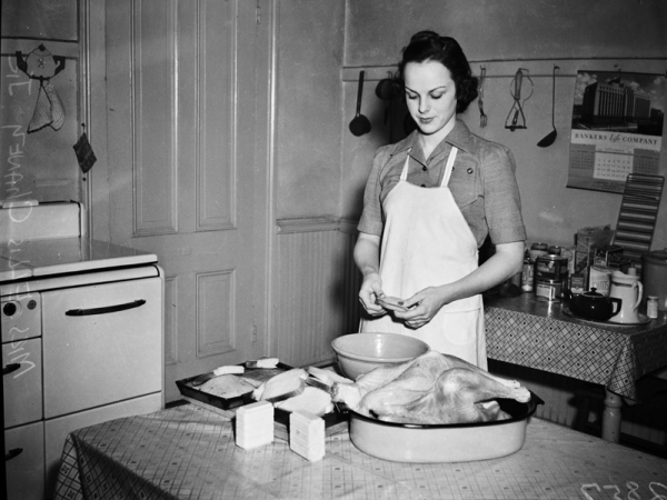 Mrs. Ellis Chaney, Jr. has her turkey day celebration at the in-between season. Pictured in her kitchen, she gives the fowl some last minute seasoning before turning on the heat, 1941, MS 359