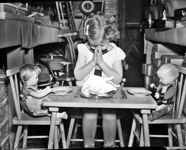 Mary Anne Koenning, three years old, is celebrating traditional feast of Thanksgiving with her dolls, 1939, MS 359