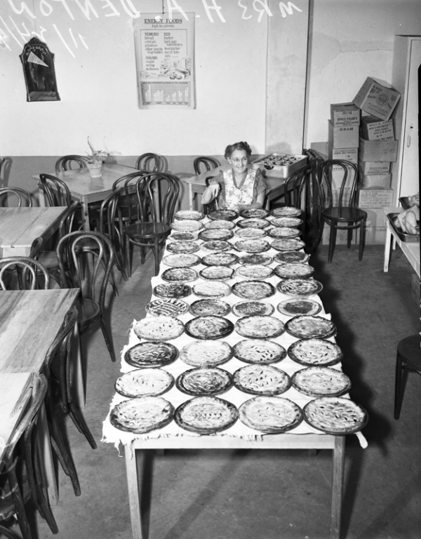 Mrs. H. A. Denton looks at a counter filled with 50 mince pies in the Hot Wells school cafeteria, 1948, MS 359