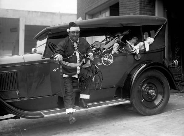 Fire Chief J. G. Sarran distributes second-hand toys that were repaired by members of the fire department, Christmas Day, 1925.   (MS 359:  L-0333-B)
