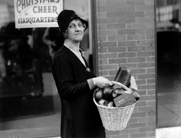 Mrs. Sam Slack, chairman of the Christmas Cheer Association, with one of the food baskets to be distributed to more than 700 needy families, 1928.  (MS 359:  L-0746-B)