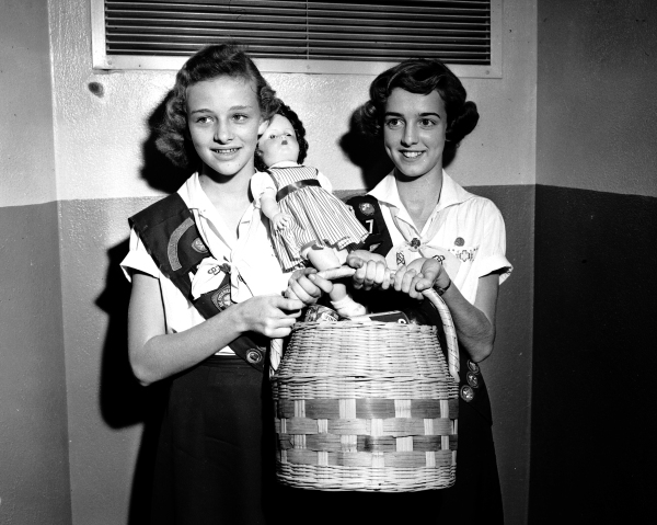 Girl Scouts Regina Leatherwood (left) and Billie Mayrant, with gift items they purchased by selling holiday cards and wrapping paper, 1955.  (MS 359:  L-4885-C)