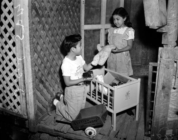 Louis Garcia, member of the Boys Club, delivers toys that were reconditioned in the Boys Club workshop, 1948.  (MS 359:  L-3683-I)