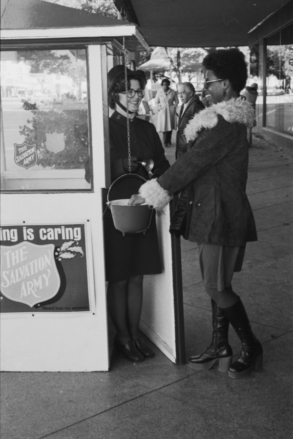 Karen McFarland, bell ringer, accepts donation from Catherine Hobbs, at Salvation Army kettle outside Joske's Department Store, 1977.  (MS 359:  L-7026-A-11)