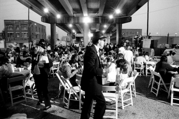 A first-class catered dinner for the homeless, sponsored by the Cordon Bleus Brothers, is served beneath the W. Commerce Street Overpass.  A blues band (background, right) performs for the crowd, Christmas Eve, 1988.  (MS 359:  L-7173-040-15)
