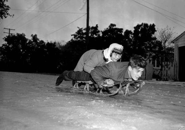 Kay Hornaday and Ray Conder use a snow sled on icy hill in Alamo Heights, December 31, 1946  (San Antonio Light Collection, MS 359: L-3333-L)