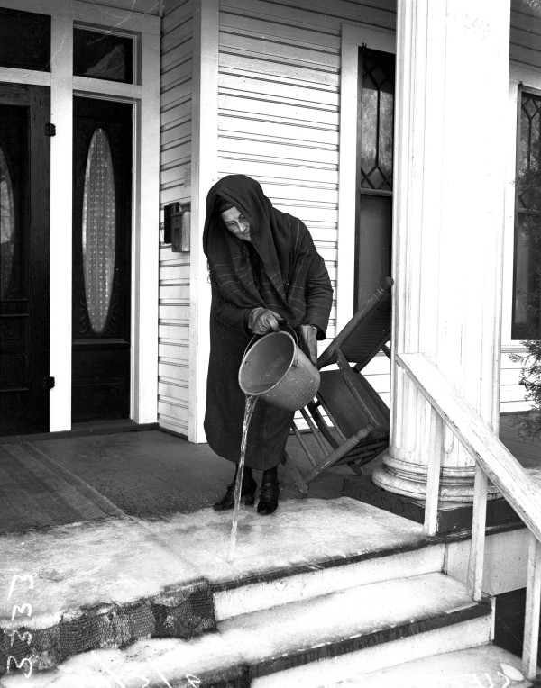 Amelia Swyers thaws the porch at apartment house at 610 Van Ness Street, January 1947.  (San Antonio Light Collection, MS 359: L-3333-N)