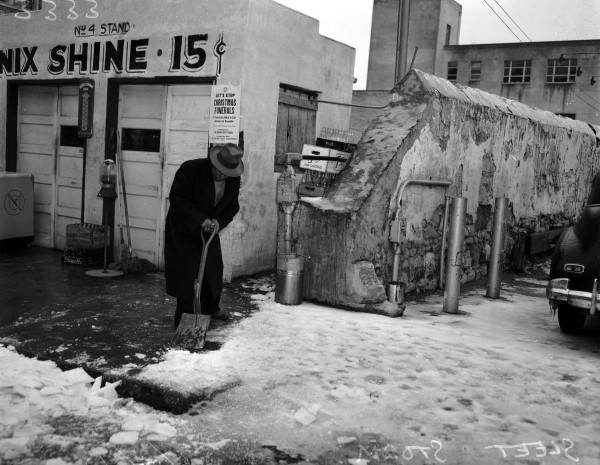 Man removes ice from a downtown sidewalk, January 1947.  (San Antonio Light Collection, MS 359: L-3333-Q)