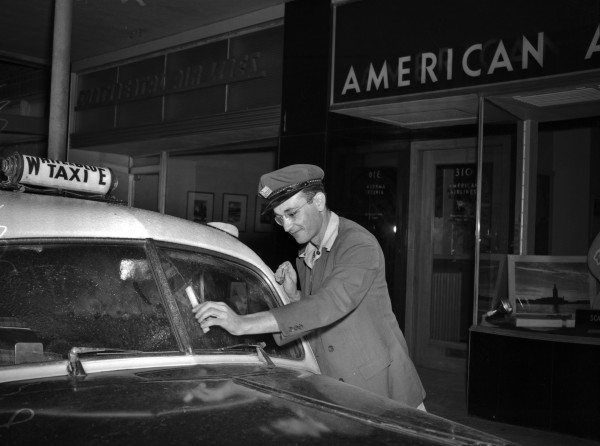 Lawrence Morriss, driver for White and Blue Cab Company, scrapes ice off his cab's windshield, January 28, 1948.  (San Antonio Light Collection, MS 359: L-3514-C)