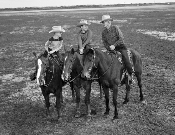 Senior participant John J. Hopkins, a Garwood area rancher who rode horseback to San Antonio before the advent of the automobile, gives advice to Oscar (left) and Les Bunge, Jr., sons of the trail boss.  (MS 355:  Z-2475-B-20)