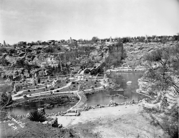 The Lily Pond, with a division between the two water levels in center foreground.  Cars are parked along Alpine Drive at the top of the cliff.  Photograph by Smith Studio, circa 1918.   (General Photograph Collection MS362:  092-0171)