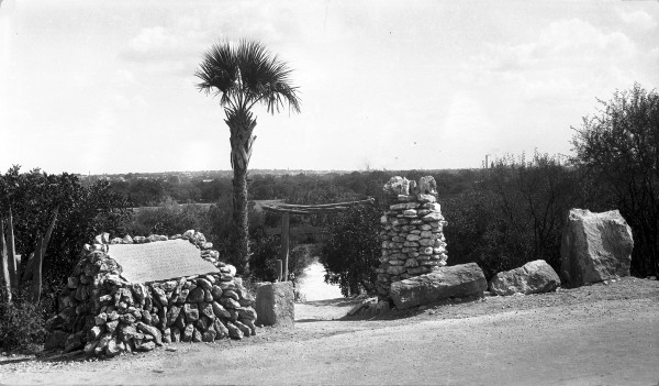 Tori Gate at Alpine Drive entrance, the main access to the garden before St. Mary's Street was extended into Brackenridge Park.  On left is a plaque with names of the lily pond donors.  Photograph by Al Schaal, circa late 1920s.  (General Photograph Collection MS 362:  109-0252)