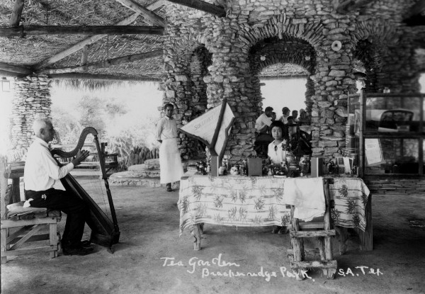 Ruth Jingu sits at table with sign advertising Sukiyaki, while regular entertainer Santana Perez plays harp, circa 1930.  (General Photograph Collection MS362:  112-025)