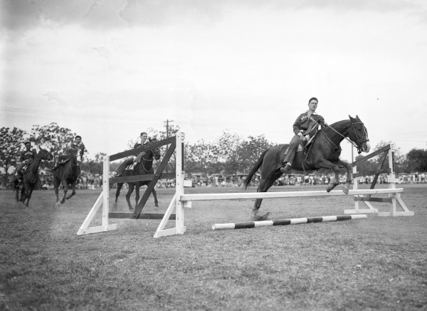 Cadet Staff Sgt. Bill Edwards leads the Peacock Monkey Drillers through a bareback acrobatic riding exhibition in front of a crowd of about 5,000 spectators.  (MS 359: L-3560-I-13)
