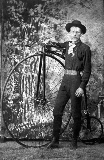 Bicyclist stands beside a high-wheeled bicycle, Flatonia, circa 1886.  (General Photograph Collection MS 362: 074-1301)
