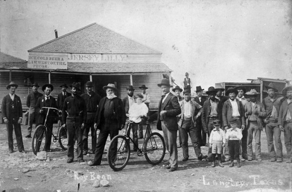 Bicyclists pose with Judge Roy Bean outside the Jersey Lilly, Langtry, 1890s.  (General Photograph Collection MS 362: 083-0871)