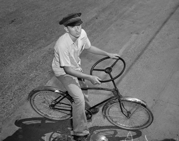 L. B. Seibel, Jr. poses with a bicycle that he improved by replacing the handle bars with an automobile steering wheel, San Antonio, June 1941.  (San Antonio Light Photograph Collection MS 359: L-2771-B)