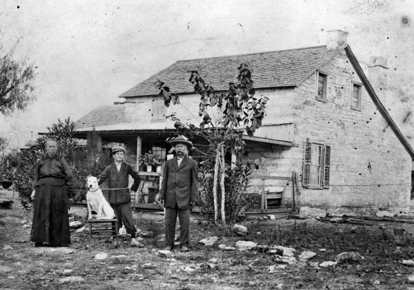 Mary Anna and Jacob Groff and their youngest child stand outside their stone farmhouse near Castroville, Medina County, circa 1910.  (MS 362: 081-0639)
