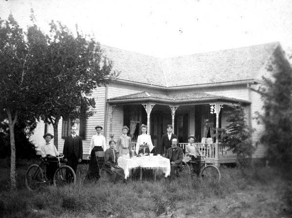 John and Johanna Rolf family and visitors pose around dining table placed directly on the native grass in their front yard, New Sweden, Travis County, circa 1905.  (MS 362: 090-0220)