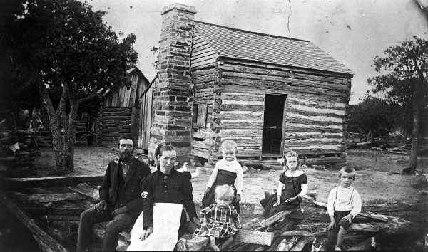 James Henry and Betty Bass and children sit on zigzag rail fence outside their single-pen log cabin on farm near Joplin, Jack County, circa 1892.  (MS 362: 093-0357)