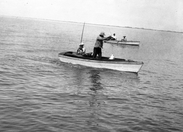 Robert M. Ayres lands a fish in a rowboat near Port Aransas, circa 1910.  Photograph by his father, Atlee B. Ayres.  (General Photograph Collection, MS 362:  084-0860)