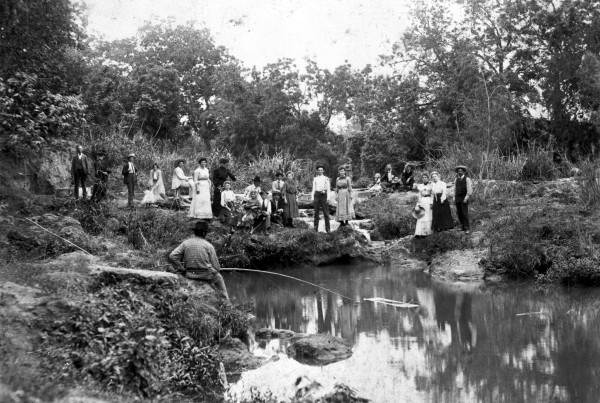 Group picnicking beside a fishing hole along the Salado Creek in southeastern Bexar County, circa 1905.  Photograph by unidentified professional photographer.  (General Photograph Collection, MS 362:  087-0059)