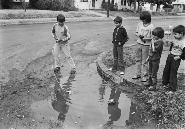Boys fishing in a pot hole at the corner of Carson and Willow Streets, San Antonio, 1984.  (San Antonio Express-News Collection, MS 360: E-207-028-37)