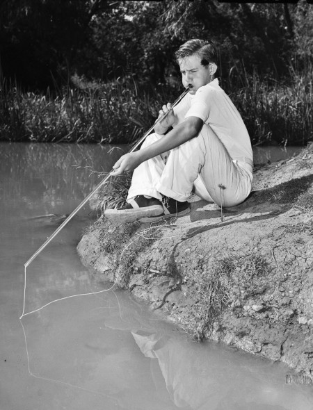 Bobby Leslie demonstrates how he blows fish out of the water with his makeshift blowgun, a section of neon tubing with a glass mouthpiece, San Antonio, 1939.  (San Antonio Light Collection, MS 359:  L-2198-B)