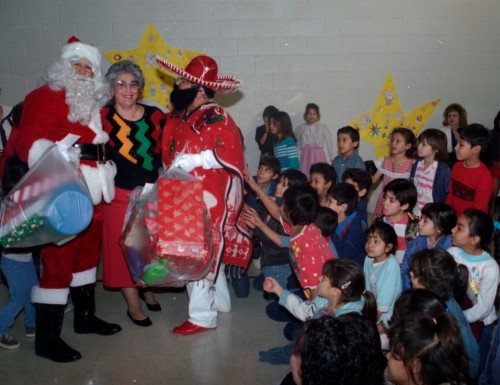 Santa Claus and Pancho Claus bring gifts for students from Storm Elementary School, 1989.  (MS 360: EN1989-12-15-24)