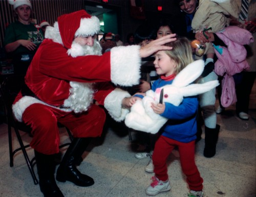 Santa Claus (Juan Esparza) distributes gifts on Christmas morning at La Villita, 1990.  (MS 360: EN1990-12-25-21)